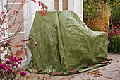 Garden furniture in the fall with green tarp wintering