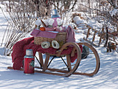 Sled in the snow with thermos, citrus and picnic basket