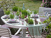 Easter table with Easter grass in cups and pots