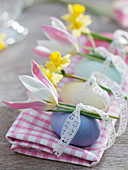 Eggs dyed with natural colors decorated with lace ribbon and flowers
