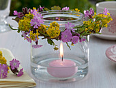 Glass as a lantern with floating candle and a Silene dioica wreath