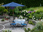 Seating with table laid under blue parasol