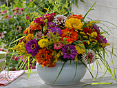 Colorful late summer arrangement in white cup