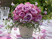 Bouquet of purple, fragrant roses with crown vines from the meadow