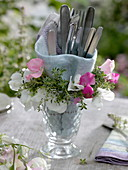 Small wreath of sweet pea and lemon thyme around glass with cutlery
