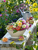 Bowl of freshly cut flowers and harvested apples
