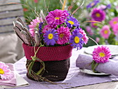 Small crocheted basket with summer asters and cutlery