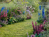 Lawn path between flowerbeds with perennials, summer flowers and grasses