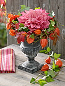 Iron amphora with dahlia flower in a spiral wreath