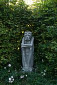 Steinerne Wächter-Figur in einer Nische der Weißbuchen - Hecke (Carpinus)