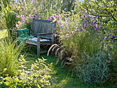 Wooden bench on the grassy bed with decorative basket