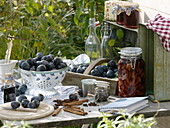 Freshly picked and canned plums on table