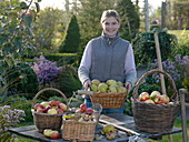 Young woman shows fruit picking in baskets