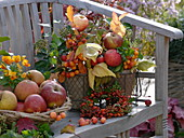 Autumn arrangement with apples, ornamental apples, rose hips and ivy