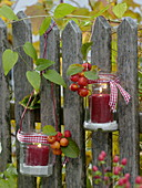 Lanterns made of jam jars with red candles and bird sand