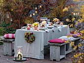 Autumn-covered table with roses and chrysanthemums bouquets
