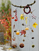 Autumn mobile made of twigs, leaves, fruits with lanterns