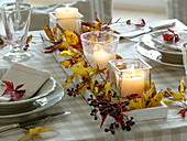Fast, autumnal table decoration with red and yellow autumn leaves