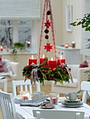 Mixed Christmas wreath with red candles hung over the table