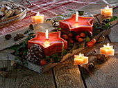Red star candles with cones, ornamental apples and hedera
