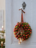 Door wreath made of moss and ornamental apples with angels and tree decorations
