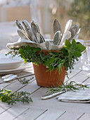 Herbs around clay pot with cutlery wreath