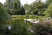 Swimming pond with wooden pier bordered with granite blocks