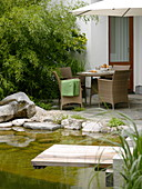 View from the swimming pond with wooden pier on terrace with wicker furniture
