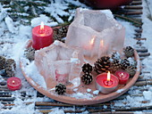 Wind lantern ice stars on terracotta coasters with cones and red candles