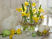 Narcissus 'Tete a Tete', small bottles as vases in a straw wreath