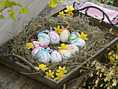 Easter basket of hay on wooden tray