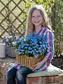 Girl holding basket with Myosotis 'Myomark' (forget-me-not)