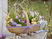 Woodchip basket as Easter basket with chocolate Easter bunny, easter eggs, carex, viola