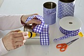 Tin cans spiced up with purple bow ribbons
