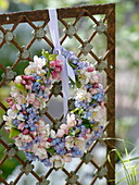 Spring flowers wreath on fence element