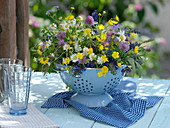 Meadow bouquet in cup in enameled colander