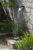 Natural stone wall with integrated waterfall