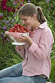 Young woman enjoying the smell of freshly picked strawberries