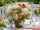 Orange-white table decoration with dahlias