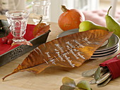 Menu card written on an autumn leaf, pumpkin, pears