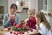 Mother and daughters making Advent wreath