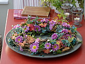 Autumn wreath made of clematis decorated with chrysanthemum