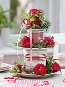 Homemade cake stand made of plates, cups and cans with roses and herbs