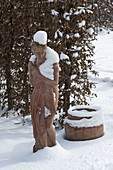 Snow-covered terracotta figurine in front of Carpinus hedge