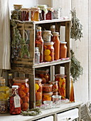 Preserved tomatoes, hot peppers, vinegar and herbs in homemade shelf