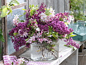 Malus flowers and syringa bouquet in glass vase