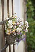 Put bouquet of roses in hanging pot on trellis