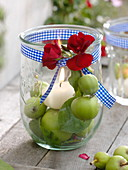 Preserving jar as a lantern with candle on green apples (Malus)