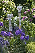 Potted cats as decorative pins on wooden posts, phlox