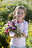 Girl with a fragrant bouquet of Lathyrus odoratus (scented vetch)
